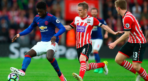 Jostle: Southampton skipper Steven Davis closes in on United's Axel Tuanzebe
