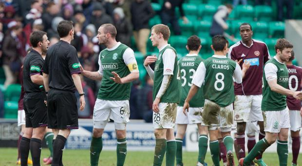 Hibernian's captain James McPake (third left) talks with referee Euan Norris (left) after the draw with Heart of Midlothian in the Clydesdale Bank Scottish Premier League match at Easter Road, Edinburgh