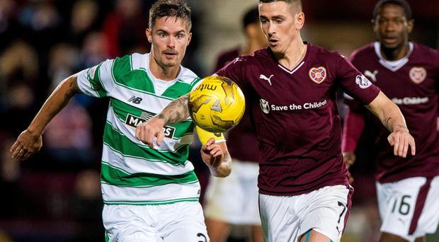 Crunch time: Celtic's Mikael Lustig and Jamie Walker of Hearts battle for the ball last night at Tynecastle