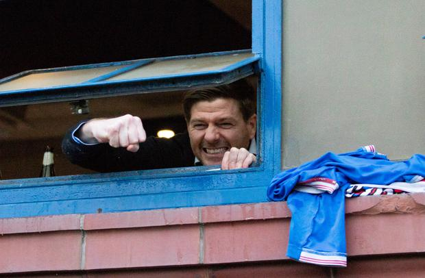 Manager Steven Gerrard waves to the fans from the dressing room window following Saturday's win over St Mirren