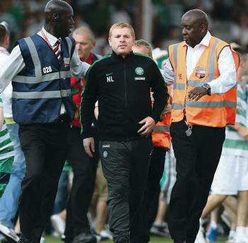 Manager of Celtic Neil Lennon is escorted off the pitch as traveling fans invade the pitch during a pre season friendly match between Brentford.