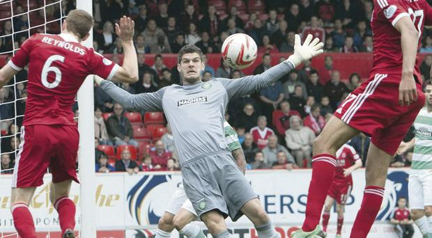 Keep out: Celtic goalkeeper Fraser Forster blocks a header from Aberdeen's Mark Reynolds (left) during Saturday's clash at Pittodrie