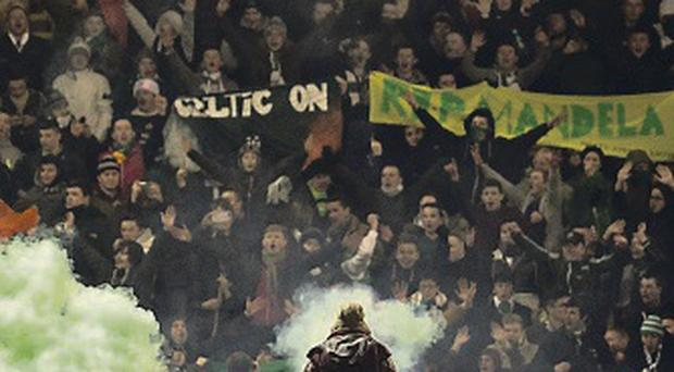 Up in smoke: A flare is thrown on the Fir Park pitch on Friday night