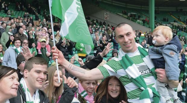 Scott Brown joins the Celtic fans to acclaim their third successive Scottish Premiership success