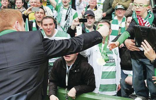 Reaching out: Celtic boss Neil Lennon hands over his medal to Jay Beatty at Parkhead