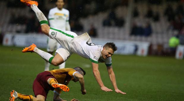 In the air: Celtic's James Forrest is sent flying after a tackle from Motherwell's Simon Ramsden, who was handed a red card