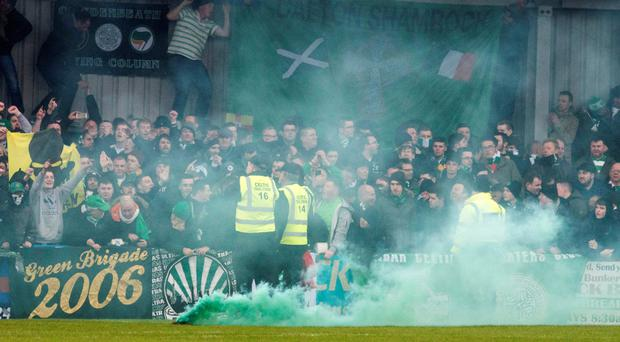 Causing a stir: Celtic fans throw smoke bombs onto the pitch, to the anger of boss Ronny Deila
