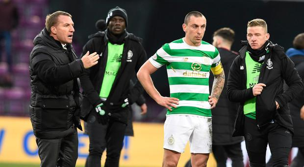 Game over: Brendan Rodgers (left) consoles his players