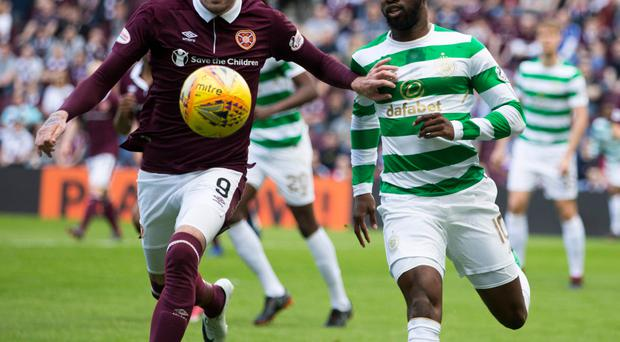 Pitch battle: Kyle Lafferty and Moussa Dembele tussle for ball