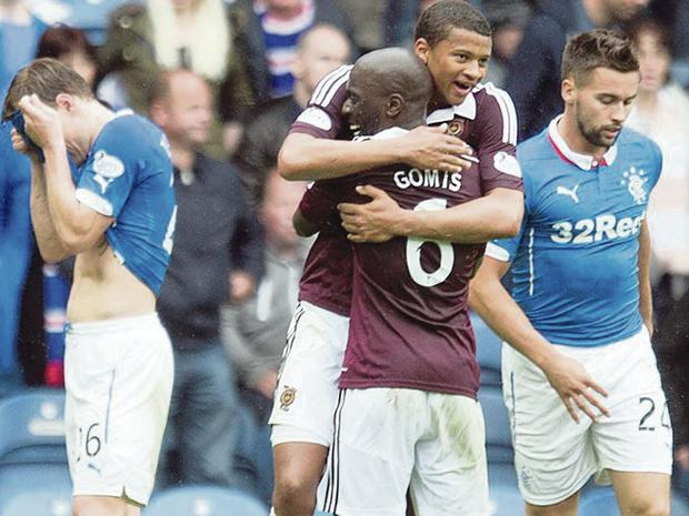 Last-gasp joy: Hearts star Osman Sow celebrates his winning goal with team-mate Morgaro Gomis to the dismay of Rangers