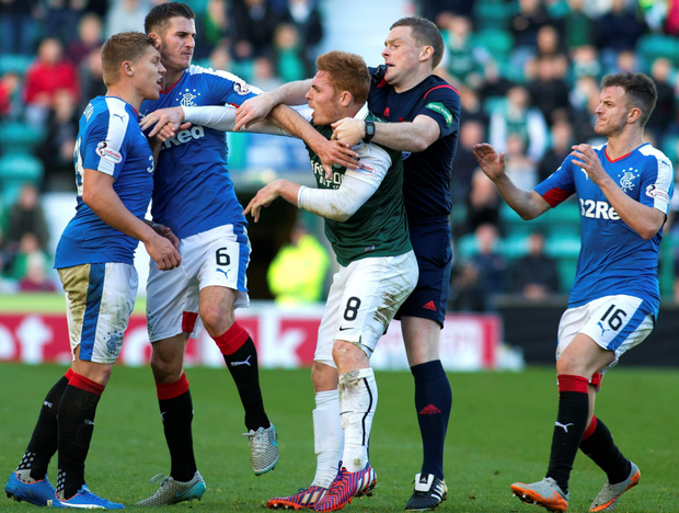 Break it up: Rangers' Martyn Waghorn and Hibernian's Fraser Fyvie have to be pulled apart by referee John Beaton