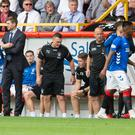 Seeing red: Rangers striker Alfredo Morelos walks past manager Steven Gerrard after being sent off