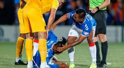 Horror moment: Alfredo Morelos comes to the aid of Joe Aribo after the midfielder suffered a nasty head injury