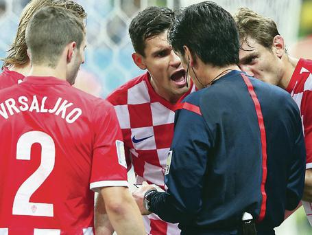 No way, ref: Yuichi Nishimura is surrounded by irked Croatia players after awarding Brazil a controversial penalty last nigh