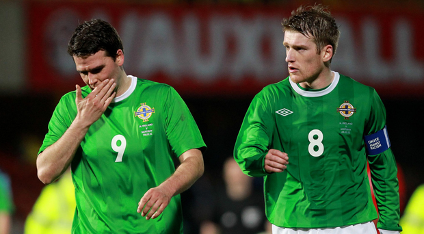 Mixed emotions: Northern Ireland's David Healy and Steven Davis after the loss to Norway in 2012 but Healy became his country's most capped outfield player on 92, passing Mal Donaghy. He finished on the 95 mark