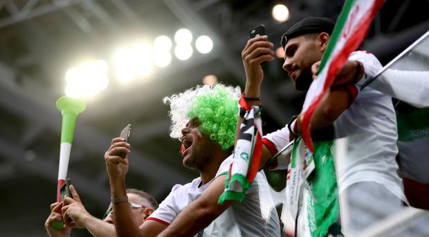 Iran fans in the stands show their support with banners, wigs and face paint
