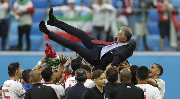 Iran head coach Carlos Queiroz is thrown into the air after his team beat Morocco (Andrew Medichini/AP)