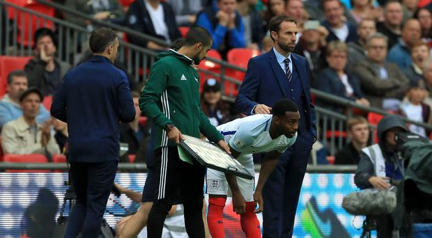 England's Danny Rose (centre) prepares to come on as a substitute alongside England caretaker manager Gareth Southgate (right)