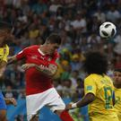 Steven Zuber, centre, heads Switzerland level against Brazil (Darko Vojinovic/AP)
