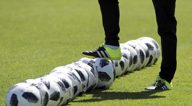 A coach prepares soccer balls prior to a training session of Japan national team at the 2018 soccer World Cup in Kazan, Russia, Friday, June 22, 2018. (AP Photo/Eugene Hoshiko)
