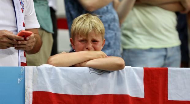 A young England fan looks on distraught after England's defeat to Iceland at Euro 2016 (Owen Humphreys/PA)