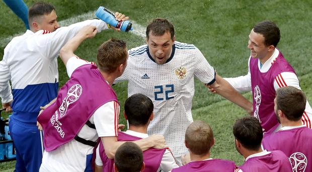 A staff member sprays water on Russia's Artyom Dzyuba as he celebrates after scoring his side's first goal by penalty during the round of 16 match between Spain and Russia at the 2018 soccer World Cup at the Luzhniki Stadium in Moscow, Russia, Sunday, July 1, 2018. (AP Photo/Vincent Michel)