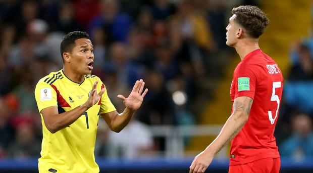 Colombia's Carlos Bacca (left) talks to England's John Stones, who has criticised Colombia's approach. (Tim Goode/PA)