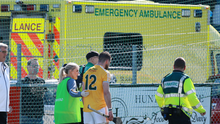 Neil McManus is led away to an awaiting ambulance after injury