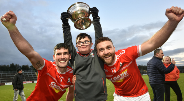Shared success: Magherafelt captain Danny Heavron and star forward Emmett McGuckin (right) join young Rossa fan Anton Campbell with the John McLaughlin trophy after Sunday's Derry SFC final