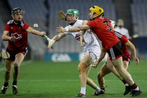 Kildare's Jack Sheridan manages to get the ball away, despite coming under pressure from two Down defenders
