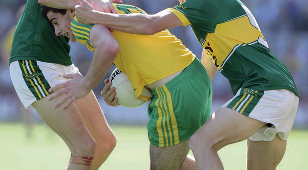 At the double: Donegal's Caolan McGonagle comes under pressure from Kerry duo Brian Sugrue and Mark O'Connor