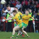 Eyes on the prize: Tyrone's Ruairi McGlone battles with Donegal's Michael Miller and Conor Morrison