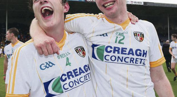 On the road: Antrim's Tiernan Coyle and Shane Dooey celebrate at the final whistle in Thurles and they'll have to go back there