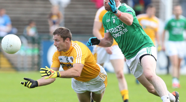 My ball: Tony Scullion of Antrim sees off the challenge of Fermanagh's Barry Mulrone