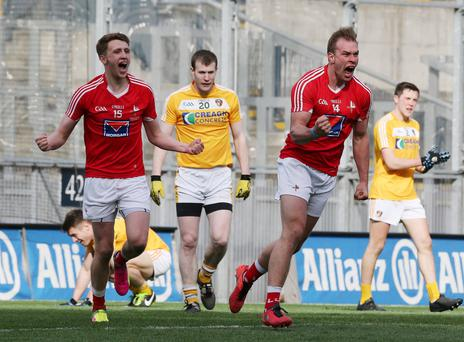 Down and out: Antrim are dejected as Conor Grimes celebrates his winning goal