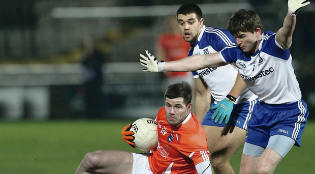 Armagh's Eugene McVerry goes down under the challenge of Monaghan's Dessie Mone