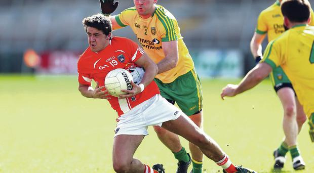 Closing in: Donegal's Eamonn McGee puts pressure on Stephen Campbell of Armagh yesterday