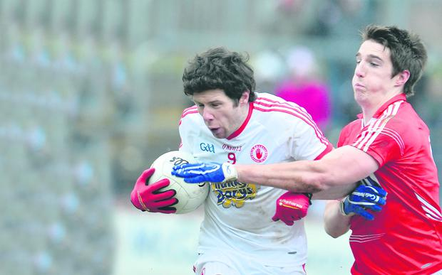 Tyrone's Sean Cavanagh resists a challenge from Aidan Walsh