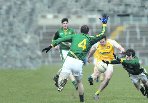 Conor Murray of Antrim is challenged by Caolan Young and Davy Dalton of Meath
