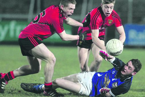 Cavan's Ciaran Brady is crowded out by Down's Michael Monan (left) and Jerome Johnston