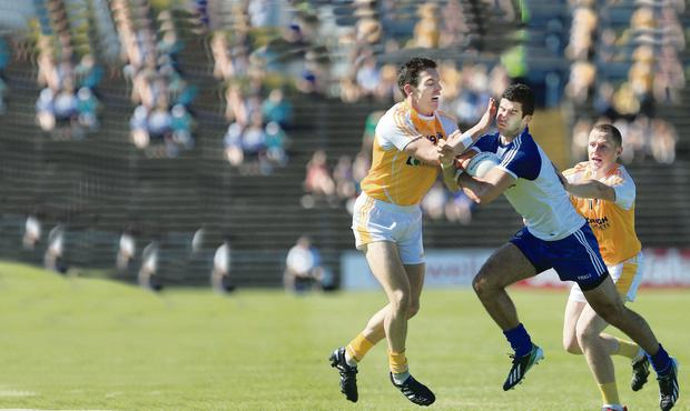 Antrim's Michael Herron and Paddy Cunningham put pressure on Monaghan's Neil McAdam