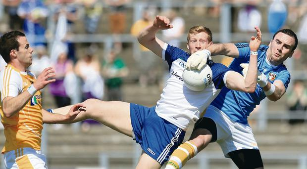 Antrim's Chris Kerr withstands a challenge from Monaghan's Kieran Hughes at Casement Park.