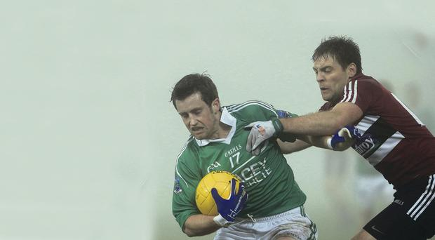 Getting shirty: St Mary's James Duffy attempts to tackle Niall McElroy of Fermanagh in the heavy fog during the clash at Brewster Park last night