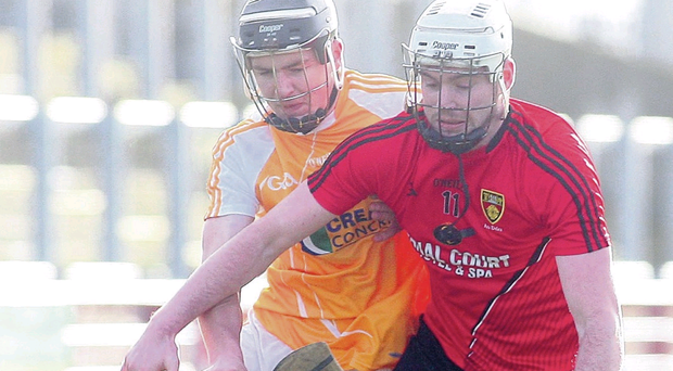 Down's Stephen Dineen holds off a challenge from Antrim's Eoghan Campbell