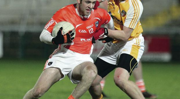 Tightly marked: Armagh's Callum Comiskey is closely watched by Kevin Quinn of Antrim during last night's thrilling clash