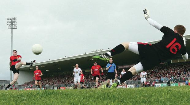 Spot on: Down's Aidan Carr powers home a penalty yesterday afternoon but Tyrone fought back to earn a replay
