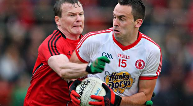 Gripping: Tyrone's Kyle Coney is tackled by Daniel McCartan