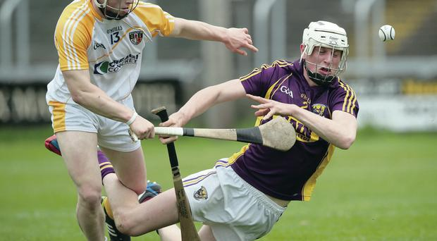 In a tangle: Antrim's Conor Johnson gets up close and personal with Liam Ryan of Wexford yesterday