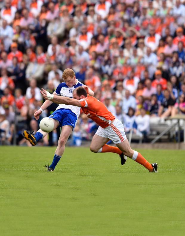 Taking flight: Armagh's Ciaran McKeever attempts to block Paudie McKenna's progress