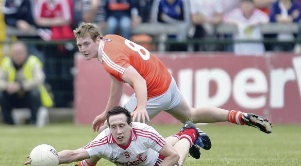 On the rise: Armagh's Kieran Toner keeps his eye on Tyrone's Colm Cavanagh